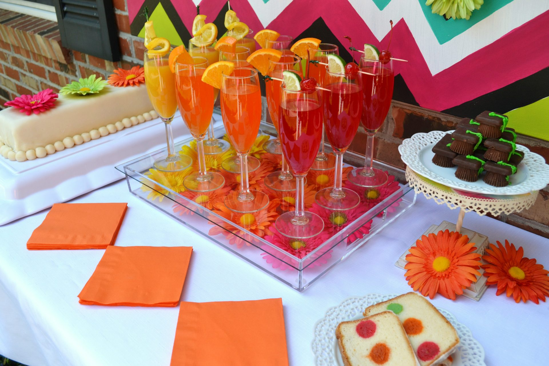 Create and host a Graduation Party with neon themed Gerber daisies, easy pick up foods and a brightly decorated table. This Graduation Party reception features a cake that is spot on with baked themed in color, cake balls inside the cake, triple lemonade and candy graduation caps.