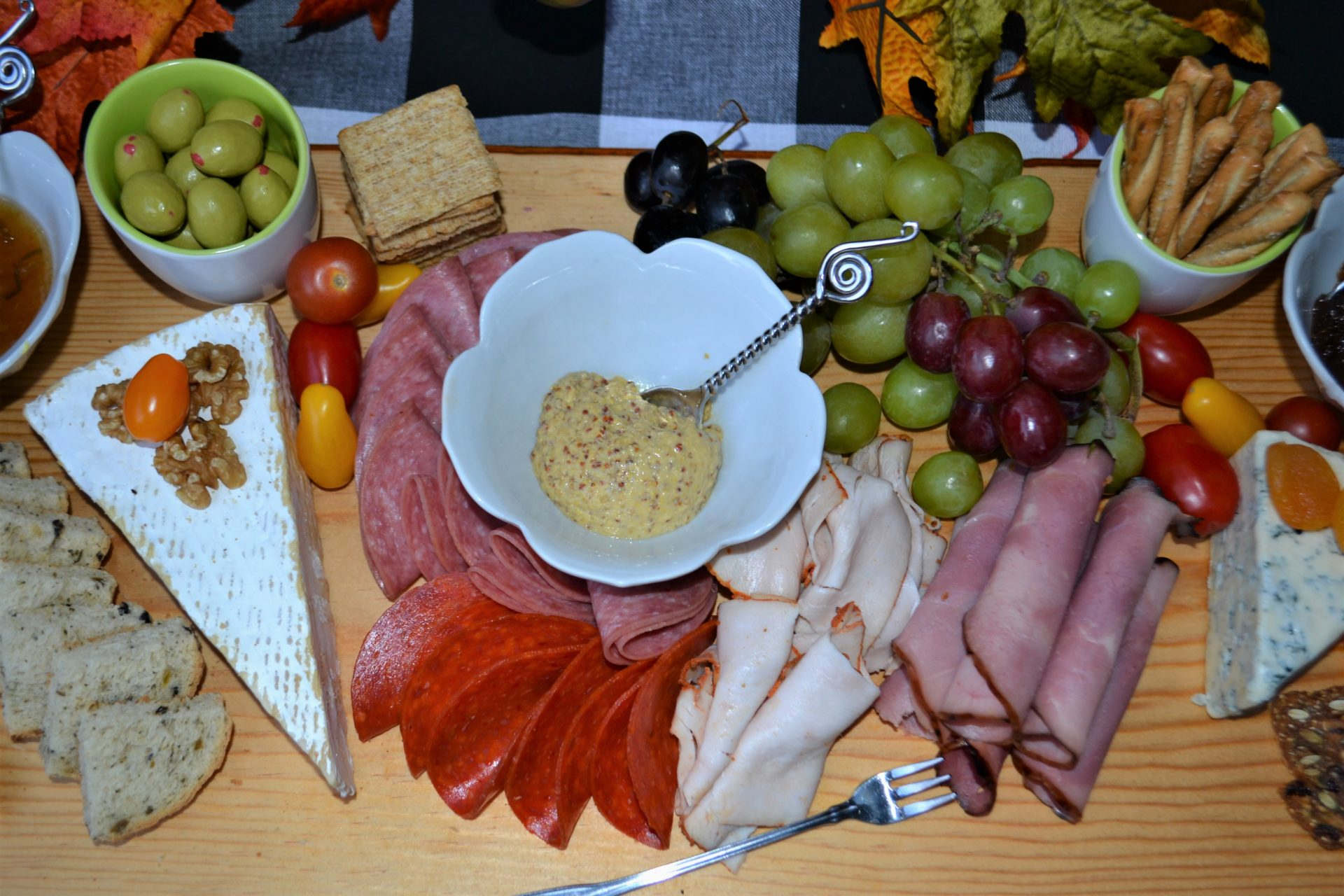 Select a large cutting board –or make one. How to on lizbushong.com Arrange trio of cheese -your choice on board. Arrange fresh fruit and spreads Nestle assorted crackers & breads that pair with the cheese and spreads Add dried fruits and nuts